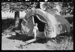 Photo: Child of white migrant going into covered wagon trail